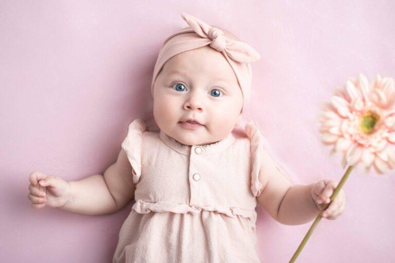 Wunderschönes Baby mit Blume in der Hand bei einem Meilenstein Fotoshooting von Siebenschön Photography in der Nähe von Ahlen